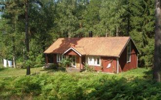 Hus mitt i skogen vid havsviken Syrsan