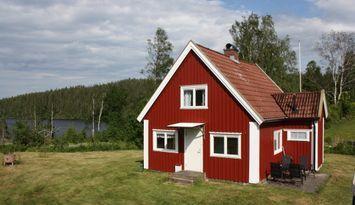 Häuschen in der Landschaft nah an einem See