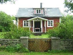 Röd stuga med vita knutar i Ardre på Gotland