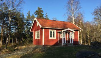 Hus i skogen vid sjö med egen brygga och roddbåt